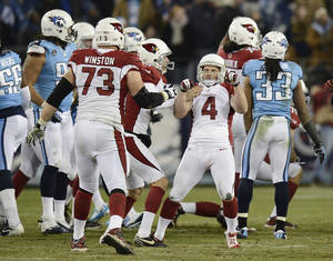 Photo - Arizona Cardinals kicker Jay Feely (4) celebrates after kicking a 41-yard field goal in overtime against the Tennessee Titans to give the Cardinals a 37-34 win in an NFL football game Sunday, Dec. 15, 2013, in Nashville, Tenn. (AP Photo/Mark Zaleski)