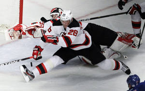 photo -   New Jersey Devils goalie Martin Brodeur, rear, and Anton Volchenkov (28), of Russia, make a save on a shot by the New York Rangers during the third period of Game 1 of their NHL hockey Stanley Cup Eastern Conference final playoff series, Monday, May 14, 2012, at New York's Madison Square Garden. (AP Photo/Julio Cortez)