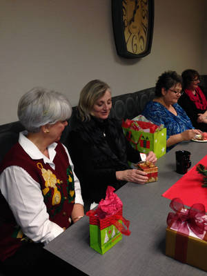 Photo - From left, GableGotwals employees Betsy Gray, Shelley Bradley, Annette Stacy and Karen Speed exchange holiday gifts on Tuesday. PHOTO PROVIDED <strong></strong>