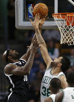 Photo - Boston Celtics' Vitor Faverani (38) blocks the shot by Brooklyn Nets' Reggie Evans (30) in the first quarter of a preseason NBA basketball game in Boston, Wednesday, Oct. 23, 2013. (AP Photo/Michael Dwyer)