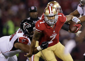 Photo - San Francisco 49ers quarterback Colin Kaepernick (7) carries the ball as Atlanta Falcons defensive tackle Corey Peters (91) grasps him during the first half an NFL football game in San Francisco, Monday, Dec. 23, 2013. (AP Photo/Marcio Jose Sanchez)