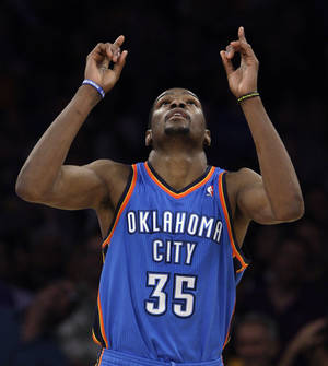 Photo - Oklahoma City Thunder forward Kevin Durant points skyward after scoring against the Los Angeles Lakers in the second overtime period of an NBA basketball game in Los Angeles, Sunday, April 22, 2012. The Lakers won 114-106 in double overtime. Durant had 35 points. (AP Photo/Reed Saxon) ORG XMIT: LAS105