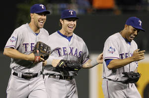 photo -   Texas Rangers center fielder Josh Hamilton, center, walks off the field with left fielder David Murphy, left, and right fielder Nelson Cruz after a baseball game against the Baltimore Orioles in Baltimore, Tuesday, May 8, 2012. Texas won 10-3. Hamilton had four home runs (AP Photo/Patrick Semansky)