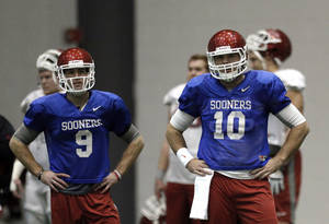 Photo - OU quarterbacks Trevor Knight, left, and Blake Bell participate in practice at the New Orleans Saints' football practice facility on Tuesday. Photo by Sarah Phipps, The Oklahoman