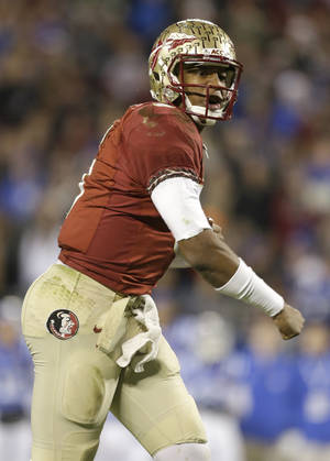 Photo - Florida State quarterback Jameis Winston reacts after a teammate's touchdown against Duke in the first half of the Atlantic Coast Conference Championship NCAA football game in Charlotte, N.C., Saturday, Dec. 7, 2013. (AP Photo/Bob Leverone)