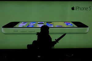 Photo - A woman holding a toy sword walks past an advertisement for the iPhone in Beijing Monday, Dec. 16, 2013. Apple Inc. might have a chance to pep up cooling iPhone sales in China if it finally can reach a deal with the world's biggest phone carrier. (AP Photo/Ng Han Guan)