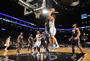 Photo - Brooklyn Nets' Brook Lopez (11) shoots over Charlotte Bobcats' DeSagana Diop (2) in the first half of an NBA basketball game on Friday, Dec., 28, 2012 at Barclays Center in New York. (AP Photo/Kathy Kmonicek)