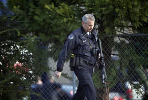 Photo - Police secure the scene of a shooting at a business park in the Fruit Valley neighborhood of Vancouver, Wash. on Monday Feb. 3, 2014. Police say at least one person was shot just before noon Monday at a Benjamin Moore Paint store in the area. (AP Photo/The Columbian, Zachary Kaufma)