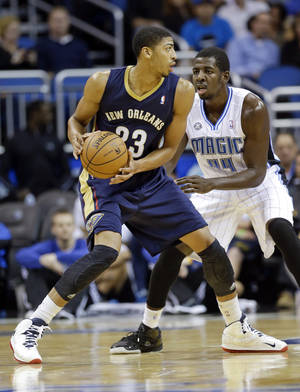 Photo - New Orleans Pelicans' Anthony Davis (23) looks for a way to the basket past Orlando Magic's Andrew Nicholson during the first half of an NBA preseason basketball game in Orlando, Fla., Friday, Oct. 25, 2013. (AP Photo/John Raoux)