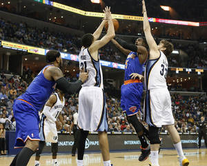 Photo - New York Knicks guard Tim Hardaway, Jr. (5) goes to the basket against Memphis Grizzlies forward Tayshaun Prince (21) and center Marc Gasol (33), of Spain, in the first half of an NBA basketball game Tuesday, Feb. 18, 2014, in Memphis, Tenn. (AP Photo/Lance Murphey)