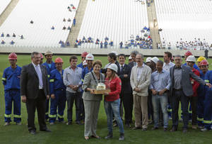 Photo - Brazil's President Dilma Rousseff, center poses for pictures with construction workers as she visits the Itaquerao stadium in Sao Paulo, Brazil, Thursday, May 8, 2014. The still unfinished stadium will host the World Cup opener match between Brazil and Croatia on June 12. (AP Photo/Andre Penner)