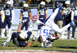 Photo - Middle Tennessee Blue Raiders running back Reggie Whatley (25) is upended by Navy Midshipmen defensive end Evan Palelei (58) on a tackled in the first half during the Armed Forces Bowl NCAA college football game, Monday, Dec. 30, 2013, in Fort Worth. (AP Photo/Matt Strasen)