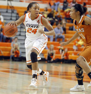 Photo - OSU: Oklahoma State's Carissa Crutchfield (24) dribbles by Texas' Chelsea Bass (11) during the women's college basketball game between Oklahoma State University and Texas at Gallagher-Iba Arena in Stillwater, Okla., Saturday, Jan. 7, 2012. Photo by Sarah Phipps, The Oklahoman