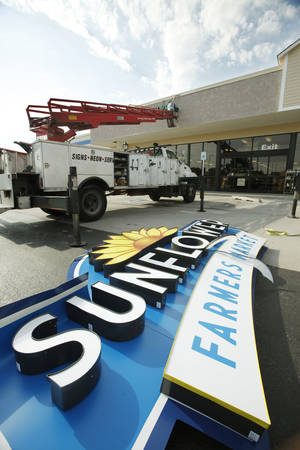 photo - Workers take down the Sunflower Market sign in Edmond. The store is changing its name this week to Sprouts. The change is a result of a merger of Sunflower and Phoenix-based Sprouts Farmers Market. The name also is changing on the Oklahoma City store at NW 63 and May Avenue.   PHOTO BY PAUL HELLSTERN, THE OKLAHOMAN