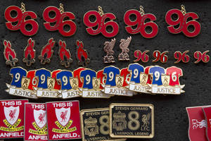 Photo - Badges commemorating the victims of the Hillsborough Disaster are seen for sale before Liverpool's English Premier League soccer match against Tottenham at Anfield Stadium, Liverpool, England, Sunday March 30, 2014. Fresh inquests into the deaths of 96 Liverpool fans who were crushed during the FA Cup semi-final at Sheffield Wednesday's Hillsborough stadium on 15 April 1989 will take place in Warrington beginning on March 31. (AP Photo/Jon Super)