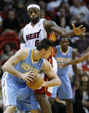 Photo -   Denver Nuggets forward Danilo Gallinari looks for an opening past Miami Heat forward LeBron James (6) during the first half of an NBA basketball game, Saturday, Nov. 3, 2012 in Miami. (AP Photo/Wilfredo Lee)