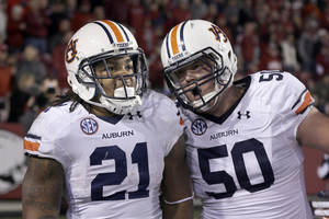 Photo - Auburn center Reese Dismukes (50) celebrates with running back Tre Mason (21) after Mason's fourth quarter touchdown in an NCAA college football game in Fayetteville, Ark., Saturday, Nov. 2, 2013. Auburn won 35-17. (AP Photo/Danny Johnston)