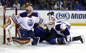 Photo - Edmonton Oilers' Martin Marincin, right, of Slovakia, falls over St. Louis Blues' David Backes as Oilers goalie Ben Scrivens, left, looks for the puck during the second period of an NHL hockey game Thursday, March 13, 2014, in St. Louis. (AP Photo/Jeff Roberson)