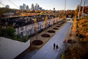 Photo -   In this Nov. 20, 2012 photo, a couple walks along the Atlanta BeltLine as the midtown skyline stands in the background in Atlanta. Since an Atlanta nonprofit opened a 2.25-mile-long paved trail east of downtown last month, it has attracted a steady stream of joggers, dog-walkers and cyclists to take in spectacular views of the skyline as well as a slice of established neighborhoods that were once only seen by riding a freight train. The Eastside Trail is the latest and most visible phase of the Atlanta BeltLine, an ambitious $2.8 billion plan to transform a 22-mile railroad corridor that encircles Atlanta into a network of parks, trails, public art, affordable homes and ultimately streetcars. (AP Photo/David Goldman)