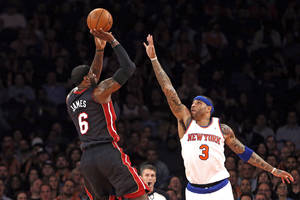Photo - Miami Heat's LeBron James (6) shoots against New York Knicks' Kenyon Martin (3) during the first half of an NBA basketball game Saturday, Feb. 1, 2014, in New York. (AP Photo/Jason DeCrow)