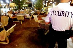 Photo - A security guard patrols an empty courtyard outside the Bricktown Sonic restaurant a few minutes after 11 p.m. as an 11 p.m. curfew for people under age 18 went into effect in Bricktown, in Oklahoma City Friday, Sept. 1, 2006. By John Clanton