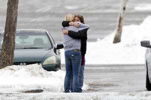 Photo - Two people embrace in the parking lot at the scene of a shooting at The Mall in Columbia on Saturday, Jan. 25, 2014 in Columbia, Md. Police say three people died in a shooting at the mall in suburban Baltimore, including the presumed gunman.(AP Photo/ Evan Vucci)