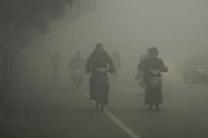 Photo - Cyclists travel on the road on a hazy day in Huaibei, in central China's Anhui province Monday Jan. 14, 2013. Air pollution is a major problem in China due to the country's rapid pace of industrialization, reliance on coal power, explosive growth in car ownership and disregard for environmental laws. (AP Photo)  CHINA OUT
