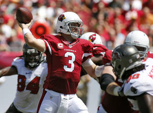 Photo - Arizona Cardinals quarterback Carson Palmer (3) throws a pass as he is pressured by Tampa Bay Buccaneers defensive end Steven Means (96), right,  during the first quarter of an NFL football game Sunday, Sept. 29, 2013, in Tampa, Fla. (AP Photo/Reinhold Matay)