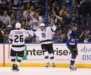 photo -   Los Angeles center Anze Kopitar (center) celebrates his second goal of the period, the Kings' fourth, with 17 seconds remaining in the first period during a second-round playoff game between the St. Louis Blues and the Los Angeles Kings on Monday, April 30, 2012, at the Scottrade Center in St. Louis. At left is Los Angeles defenseman Slava Voynov and at right is Blues left wing David Perron. (AP Photo/Post Dispatch, Chris Lee)