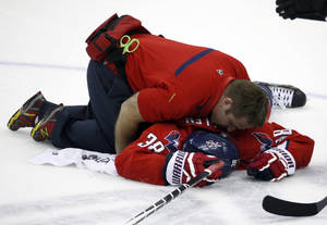 Photo - Washington Capitals trainer Greg Smith tends to defenseman Jack Hillen, after Hillen's collision with right wing Alex Ovechkin (8), from Russia, in the overtime portion of an NHL hockey game against the Los Angeles Kings, Tuesday, March 25, 2014, in Washington. The Kings won 5-4 in a shootout. (AP Photo/Alex Brandon)
