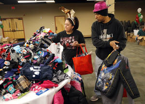 photo - U.S. Air Force Tech Sgt. Steve Monje and Jessica Monje shop for Christmas gifts Tuesday at Operation Homefront distribution center at the Reed Center in Midwest City.