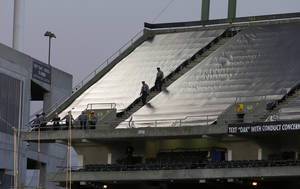 Photo - Law enforcement officials walk in the upper deck of O.co Coliseum after an NFL football game between the Oakland Raiders and the Tennessee Titans in Oakland, Calif., Sunday, Nov. 24, 2013. Authorities say a football fan jumped after the game from the third deck of the Oakland Coliseum, injuring herself and a man one level below who tried to catch her. She and the man who tried to catch her were rushed to the hospital for treatment. (AP Photo/Jeff Chiu)