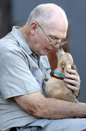 Photo - Inmate Bill Miller gets a kiss from Stanley at the Lexington Assessment and Reception Center. PHOTO BY SARAH PHIPPS, THE OKLAHOMAN <strong>SARAH PHIPPS - SARAH PHIPPS</strong>