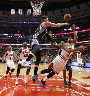 Photo - Memphis Grizzlies forward Mike Miller, front left, blocks the shot of Chicago Bulls guard D.J. Augustin (14) as Bulls' Jimmy Butler (21) and Nazr Mohammed (48) watch during the first half of an NBA basketball game on Friday, March 7, 2014, in Chicago. (AP Photo/Charles Rex Arbogast)