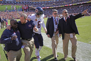 Photo - Chicago Bears quarterback Jay Cutler walks off the field after being injured by a sack from Washington Redskins defensive end Chris Baker during the first half of a NFL football game in Landover, Md., Sunday, Oct. 20, 2013. (AP Photo/Alex Brandon)