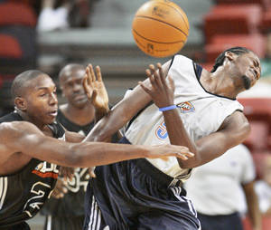 Photo - Oklahoma City's Kyle Weaver, right, and the Bulls' DeMarcus Nelson collide during their Summer League game in Las Vegas on Friday. Chicago won 80-74. AP PHOTO