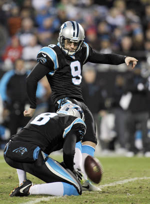 Photo - FILE - In this Dec. 15, 2013 file photo, Carolina Panthers' Graham Gano (9) kicks a field goal against the New York Jets during the first half of an NFL football game in Charlotte, N.C. Holding the ball is punter Brad Nortman. Gano is the first of Carolina's 20 soon-to-be unrestricted free agents to re-sign with the Panthers. Carolina announced Friday, Feb. 28, 2014, that Gano agreed to a four-year contract. (AP Photo/Bob Leverone)