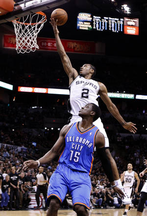 Photo - San Antonio's Kawhi Leonard (2) shoots a lay up as Oklahoma City's Reggie Jackson (15) looks on during Game 1 of the Western Conference Finals in the NBA playoffs between the Oklahoma City Thunder and the San Antonio Spurs at the AT&T Center in San Antonio, Monday, May 19, 2014. Photo by Sarah Phipps, The Oklahoman