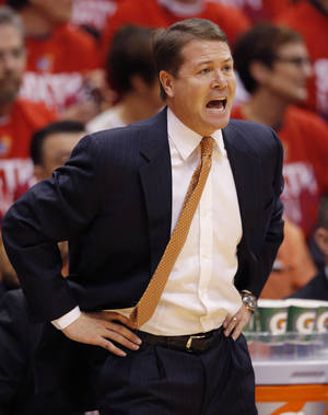 Photo - Oklahoma State head coach Travis Ford yells to his team during the first half of an NCAA college basketball game against Kansas at Allen Fieldhouse in Lawrence, Kan., Saturday, Jan. 18, 2014. (AP Photo/Orlin Wagner)