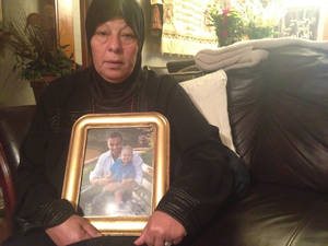 photo - Jasen Yousif's mother, Annie, holds a picture of her son as the family grieves together on Monday at home in Oklahoma City. Yousif was killed Friday in a shooting at a northwest Oklahoma City Target store parking lot during what police said could be a road rage incident.   <strong>Juliana Keeping, The Oklahoman</strong>
