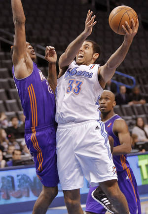 Photo - Tulsa's Grant Jerrett (33) drives to the basket against Iowa's Larry Owens (23) during the NBA Developmental game between the Tulsa 66ers and the Iowa Energy at the Chesapeake Energy Arena in Oklahoma City, Okla. on Tuesday, Feb. 4, 2014. Photo by Chris Landsberger, The Oklahoman