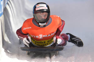 Photo - Latvia's winner Martins Dukurs arrives in the finish area after the second run at the men's Skeleton World Cup race in Innsbruck, Austria, Saturday, Jan. 18. 2014. (AP Photo/Kerstin Joensson)
