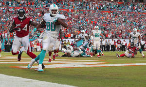 Photo - Miami Dolphins tight end Dion Sims (80) scores a touchdown for the win against the Atlanta Falcons during the second half of an NFL football game at Sun Life Stadium, Sunday, Sept. 22, 2013, in Miami Gardens, Fla. (AP Photo/El Nuevo Herald, Hector Gabino) MAGS OUT.
