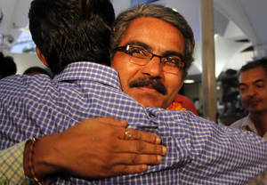 Photo -   Shantilal Harji Solanki, one of the seven Indian crew members of the Italian ship Enrica Ievoli, which was hijacked by Somali pirates, and were held hostage for four long months, hugs a colleague upon his arrival at the airport in Mumbai, India, Tuesday, May 1, 2012. The ship was carrying 15,000 metric tons of caustic soda from Iran to Turkey when it was hijacked by Somali pirates. (AP Photo/ Rajanish Kakade)