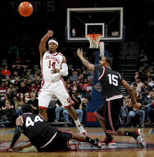 Photo - OU's Carl Blair Jr. passes the  ball from between Cincinnati's JaQuon Parker, left, and Darnell Wilks during the All-College Classic basketball game between the University of Oklahoma and Cincinnati at the Oklahoma City Arena on Saturday, December 18,  2010.   Photo by Bryan Terry, The Oklahoman