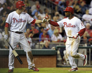 Photo -   Philadelphia Phillies' Chase Utley, left, greets Jimmy Rollins, right, as he crosses the plate to score on a ground ball from Juan Pierre against the Miami Marlins in the fifth inning of a baseball game, Tuesday, Sept. 11, 2012, in Philadelphia. (AP Photo/The Express-Times, Matt Smith)