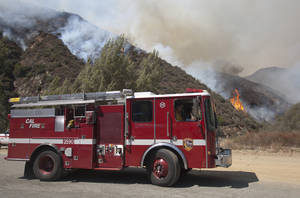 photo -   A fire engine pulls away as firefighters fight a wildfire in the Angeles National Forest north of Glendora, Calif. Monday, Sept. 3, 2012. A day after the wildfire broke out near a campground and forced the evacuation of thousands of campers and picnickers it had grown to more than 4,100 acres, or roughly 6 square miles, and was just five percent contained. (AP Photo/Jason Redmond)  