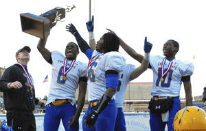 Photo - LaQuon Treadwell, second from left, holds the championship trophy after helping Crete-Monee win the Illinois Class 6A high school championship on Nov. 24. AP PHOTO
