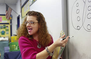 Photo - Sallie Harrison, a fourth-grade science and math teacher at Meeker Elementary School, explains long division to her students. Harrison has has multiple sclerosis.    Photo by Jim Beckel, The Oklahoman <strong>Jim Beckel - THE OKLAHOMAN</strong>