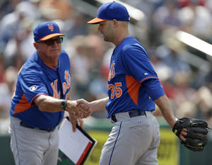 Photo - New York Mets pitching coach Dan Warthen, left, congratulates pitcher Dillon Gee (35) after he was pulled in the sixth inning of an exhibition baseball game against the Minnesota Twins in Fort Myers, Fla., Friday, March 21, 2014. (AP Photo/Gerald Herbert)